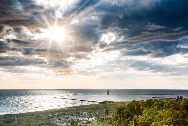 Sun through clouds over Lake Michigan and Frankfort harbor.
