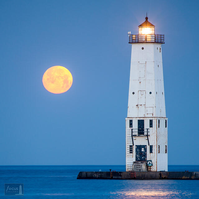 Full moon setting over Frankfort Lighthouse and Lake Michigan.