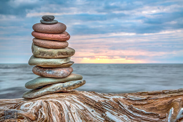 Photograph of a cairn (stack of rocks) on a driftwood log with Lake Superior and the sunset behind.