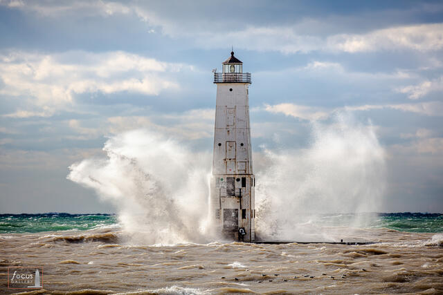 Lake Michigan waves crash against the Frankfort North Breakwater Lighthouse, Frankfort, Benzie County, Michigan