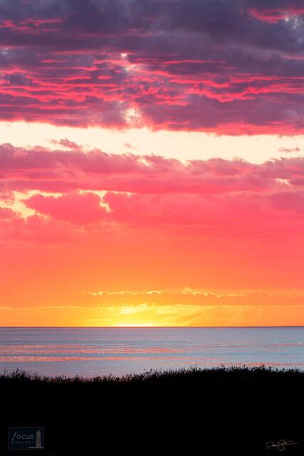 Vivid sunset over dune grasses and Lake Michigan at Platte River Point, Sleeping Bear Dunes.