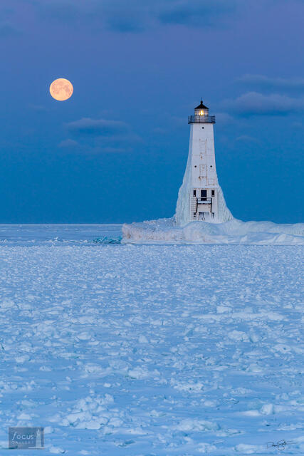 Full moon sets over frozen Lake Michigan at Frankfort.