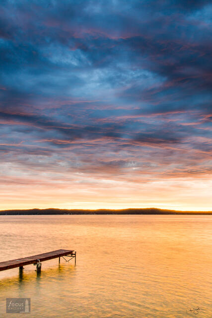 Colorful sunrise over Platte Lake with a dock.