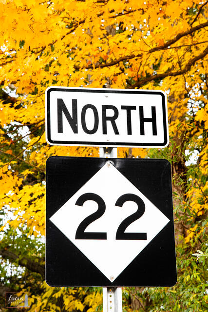 M22 North Scenic Highway sign with autumn colors behind.