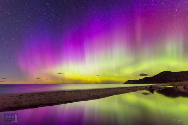 Colorful display of aurora borealis over Otter Creek and Lake Michigan in the Sleeping Bear Dunes National Lakeshore.