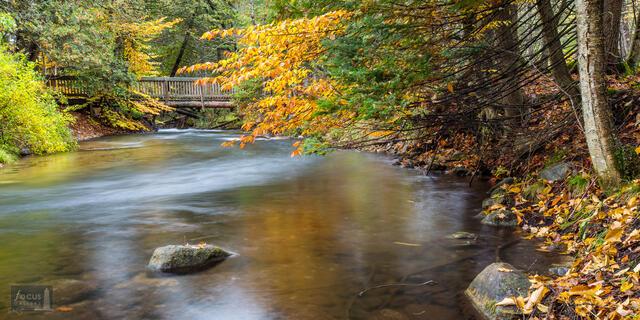 Rustic bridge over Rapid River in autumn, Seven Bridges Nature Area, Kalkaska County, Michigan.