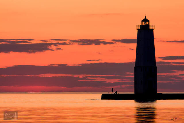 Sunset over Lake Michigan as two visitors watch from the Frankfort Lighthouse.
