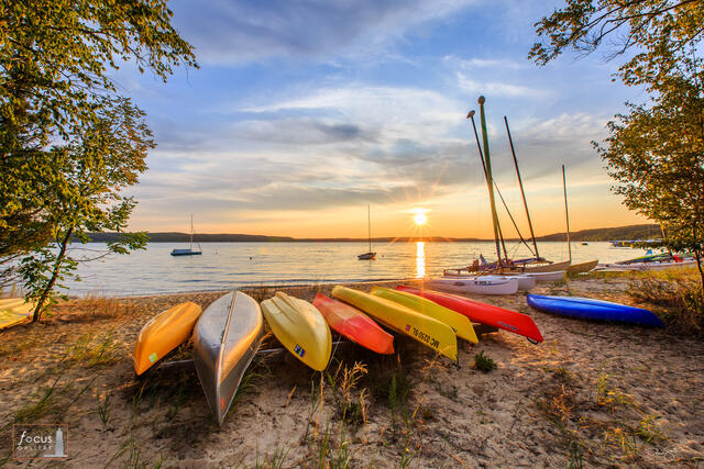 Sunset over Crystal Lake beach with canoes, kayaks and sailboats on the beach.