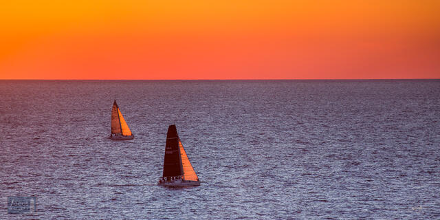 Two sailboats on Lake Michigan with sunset glow in the sky.
