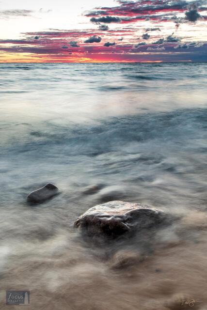 Lake Michigan waters and boulder at sunset.