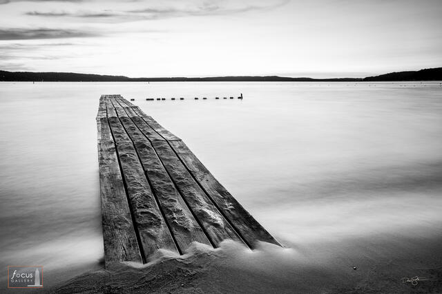 Black and white photograph of an old wooden dock at sunrise on Crystal Lake, Michigan.