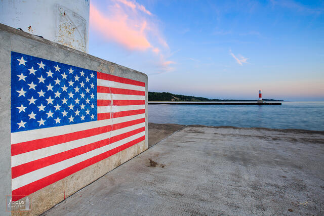 Painting of the American Flag on the base of the Portage Point Lighthouse in Onekama, Michigan at sunset.