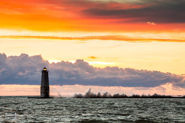 Large waves crash against the Frankfort North Breakwater Lighthouse during a colorful sunset.