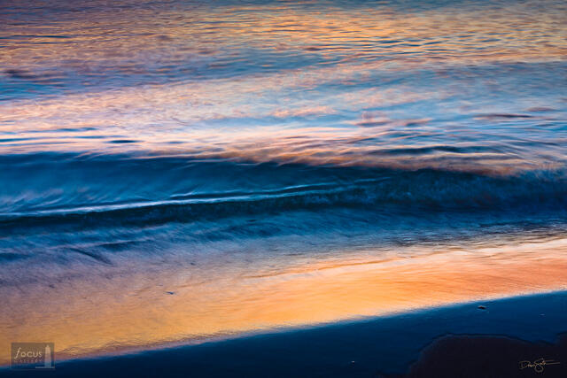 Colors of sunset reflected on waves at the shore of Lake Michigan.