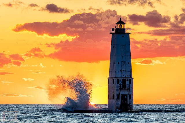 Waves crash at sunset with the Frankfort North Breakwater Lighthouse and colorful clouds.