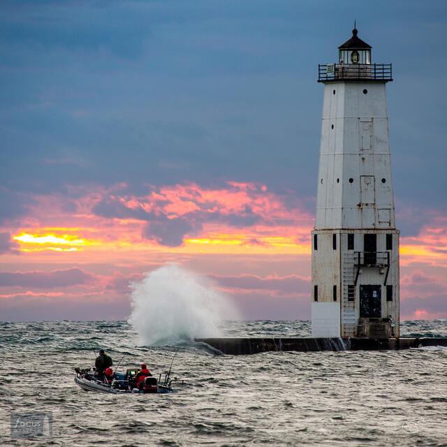 Fishing boat at sunset on Lake Michigan with waves crashing at Frankfort lighthouse.