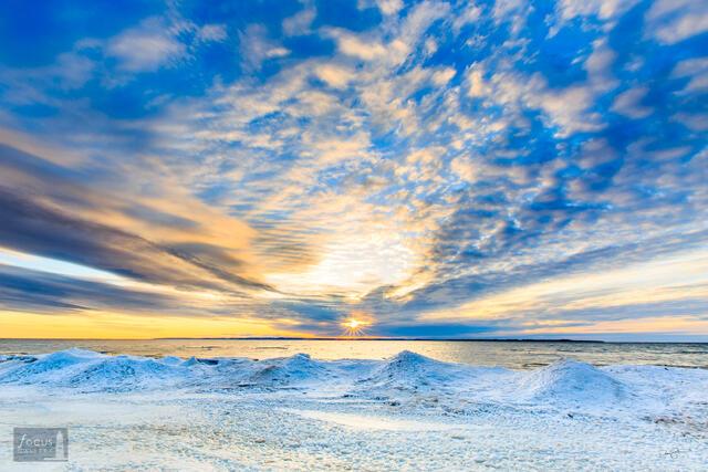 Winter sunset over icy shoreline of Lake Michigan.