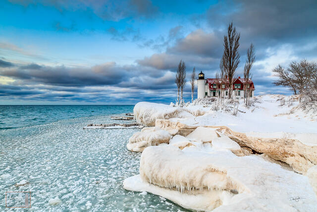 Snowy winter shoreline at Point Betsie with ice on Lake Michigan.