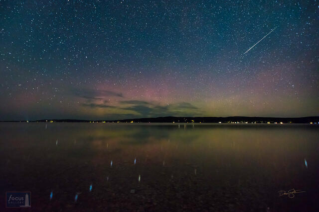 Starry skies with Big Dipper and a meteor reflecting on Crystal Lake with aurora borealis.