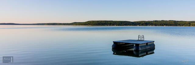 Swimming platform on Crystal Lake at dawn with blue sky and water.