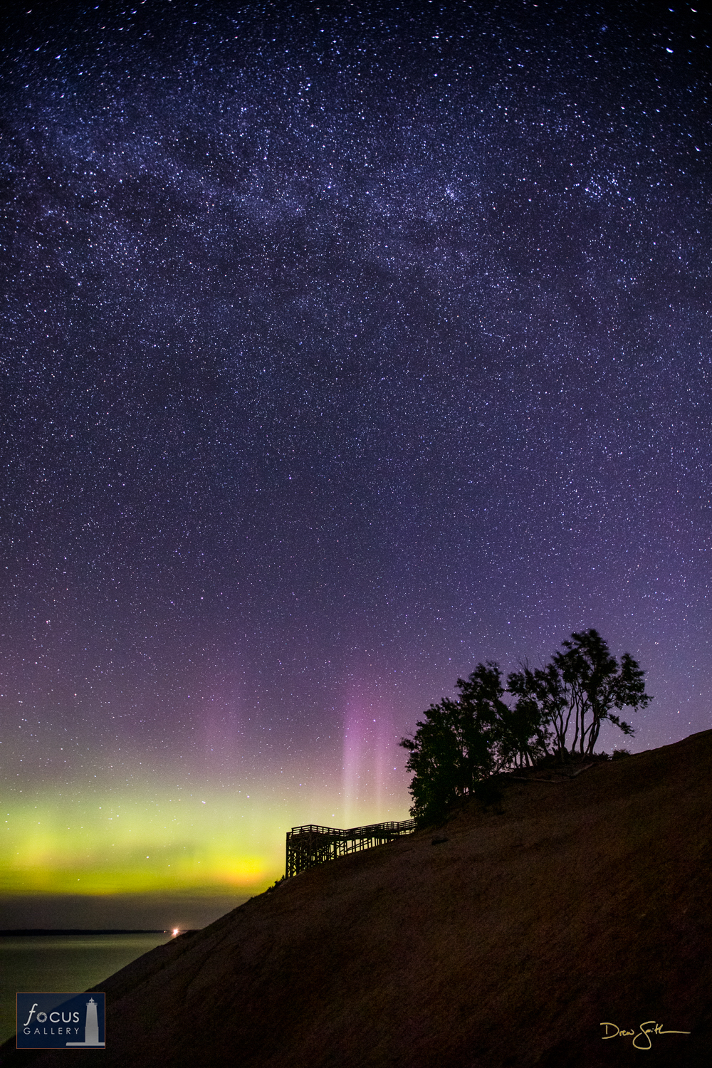 Photo © Drew Smith Pillars of light rise up into the starry night sky from the glow of aurora borealis over Sleeping Bear Dune...