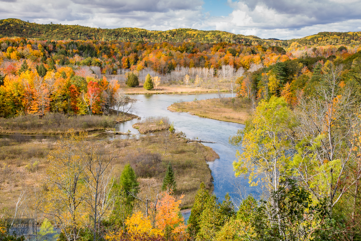 View of a bend in the Manistee River in fall colors.