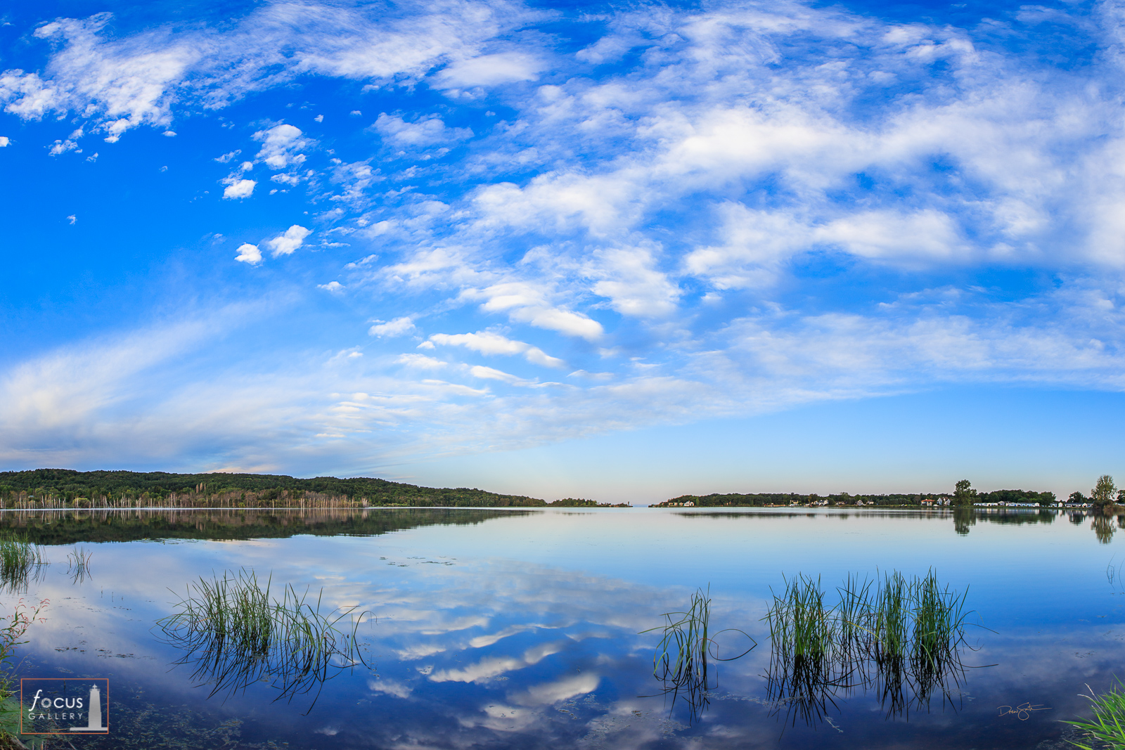 Blue sky and clouds reflected on Arcadia Lake, Arcadia, Michigan.