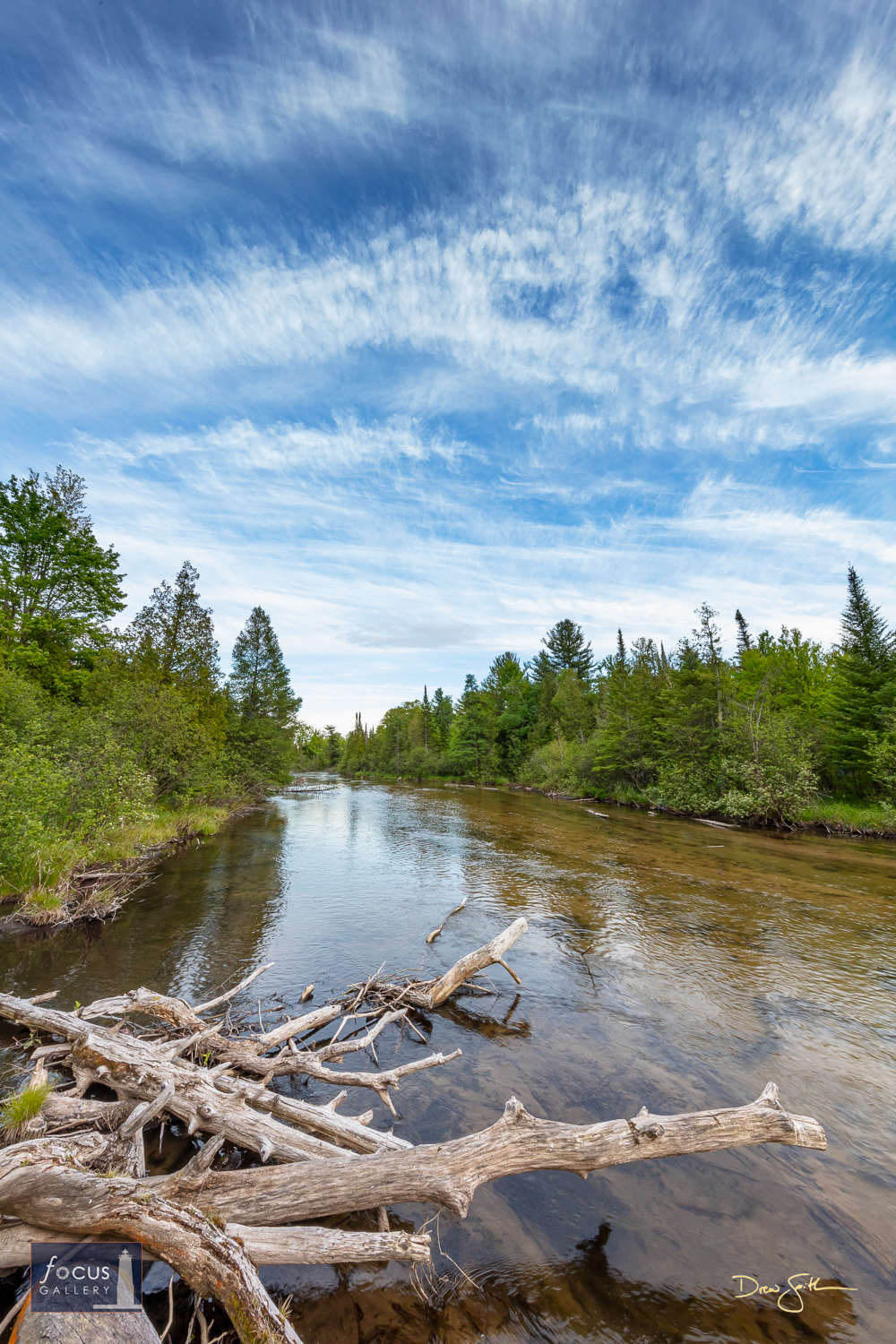 Photo © Drew Smith The blue sky is filled with wispy cirrus clouds above the Platte River at Platte River Park. This image was...
