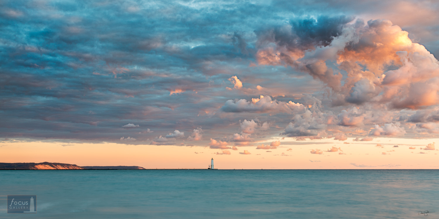Frankfort Lighthouse and Lake Michigan and colorful clouds.