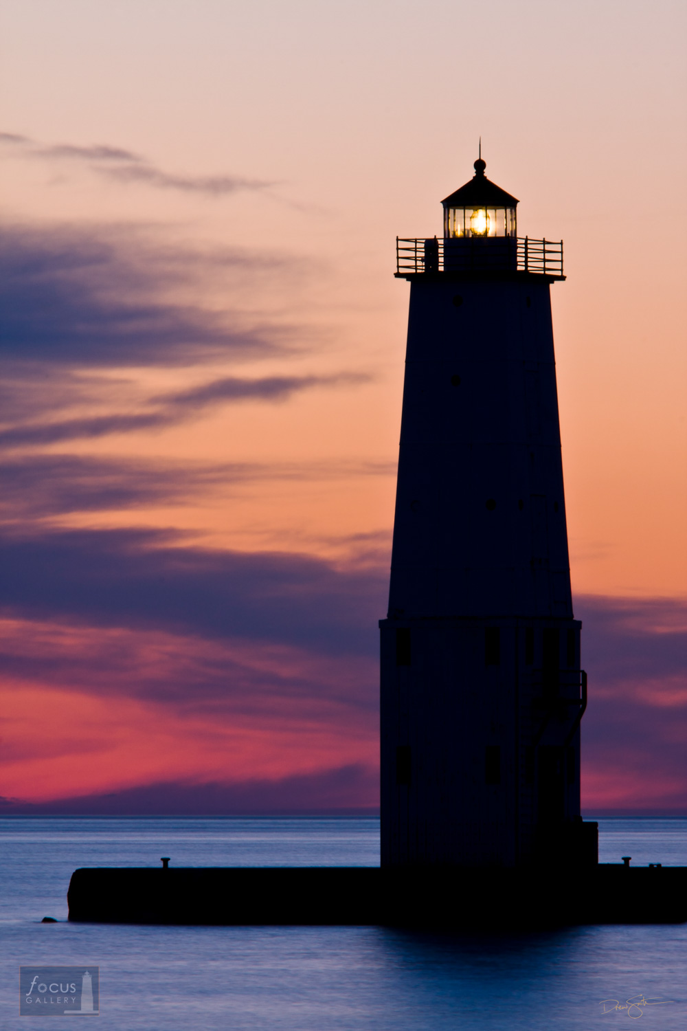 Colorful sunset and the silhouette of the Frankfort Lighthouse.