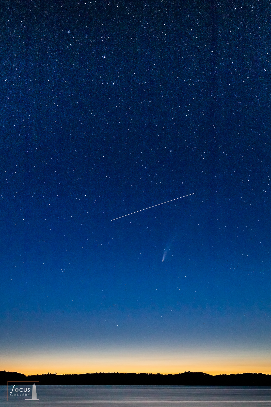The International Space Station passes between Comet NEOWISE and the Big Dipper over Lower Herring Lake, Benzie County, Michigan.