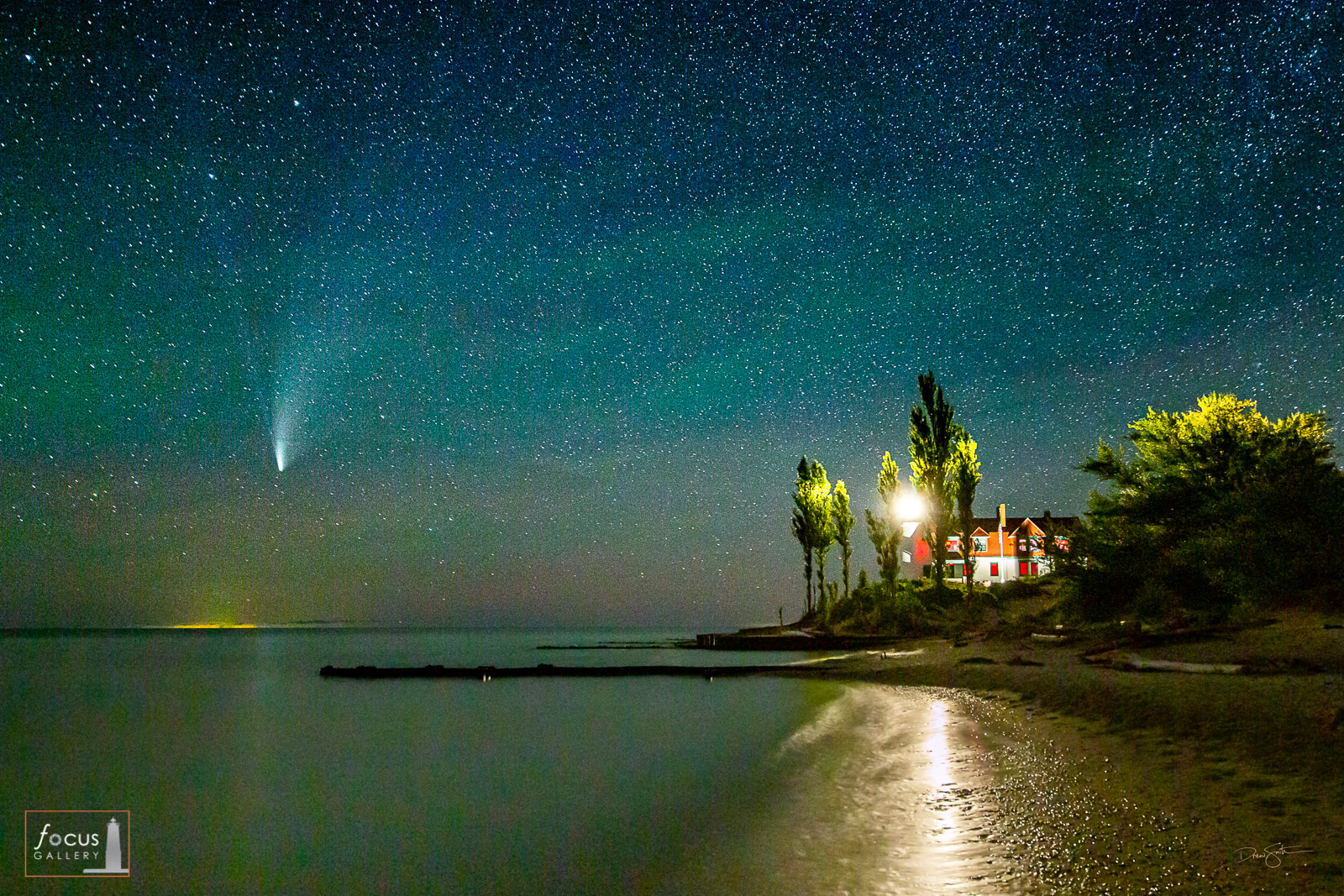 Comet NEOWISE in a starry sky over Lake Michigan at Point Betsie Lighthouse, Michigan.