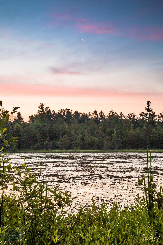 Crescent moon and sunrise colors over Pyatt Lake, Michigan.