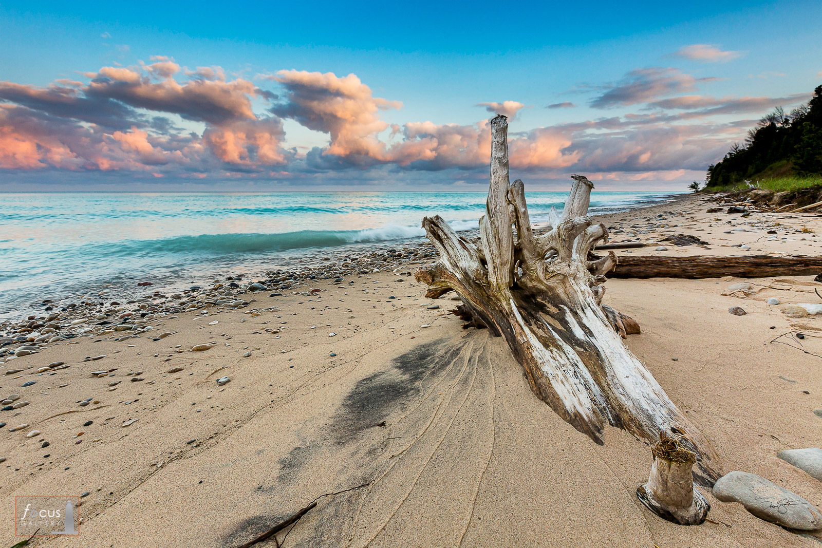 Driftwood log on the Lake Michigan beach with pretty clouds and sky behind.