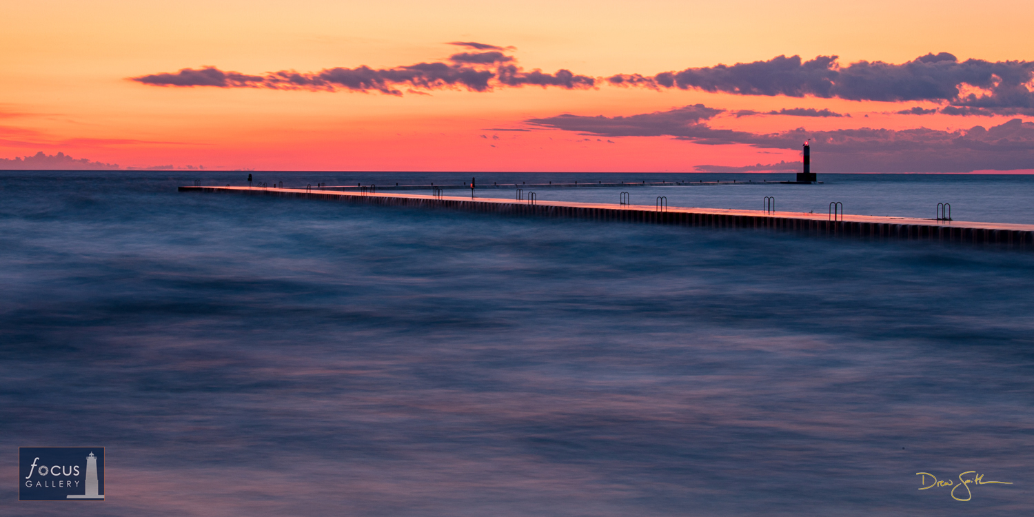 Photo © Drew Smith The last light of the fading sunset glows pink and orange above the Elberta pier as the waters of Lake Michigan...