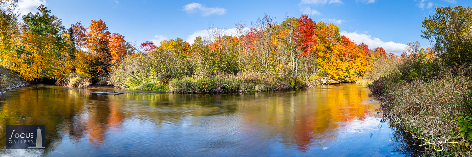 Photo © Drew Smith Fall colors are reflected on the surface of the Betsie River as it meanders around a bend.