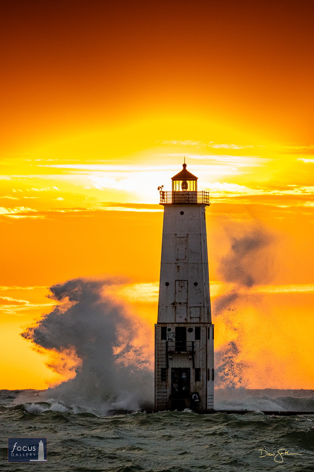 Photo © Drew Smith The sun shines behind the Frankfort Lighthouse as big waves crash, nearly reaching the top of the 70-foot...