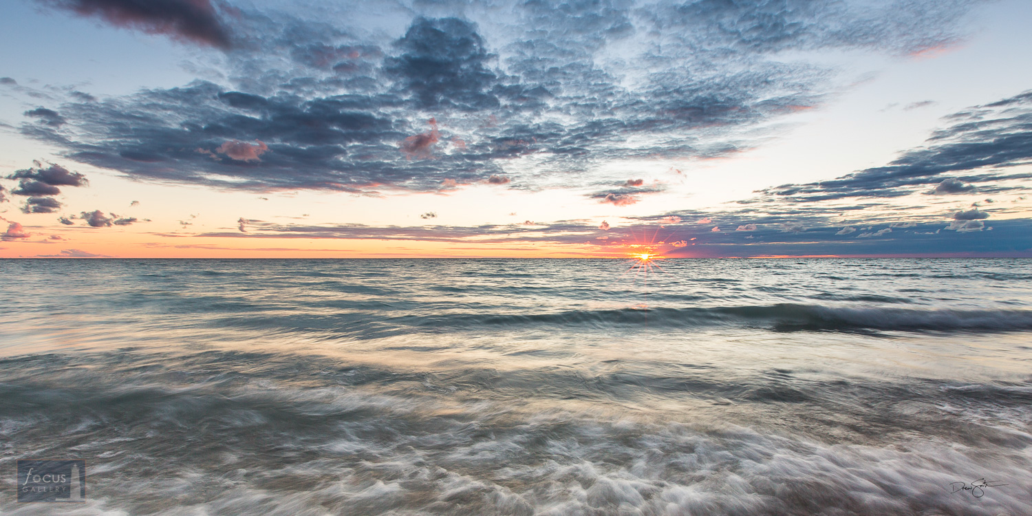 Panoramic sunset over Lake Michigan with blue water and skies and orange sun.