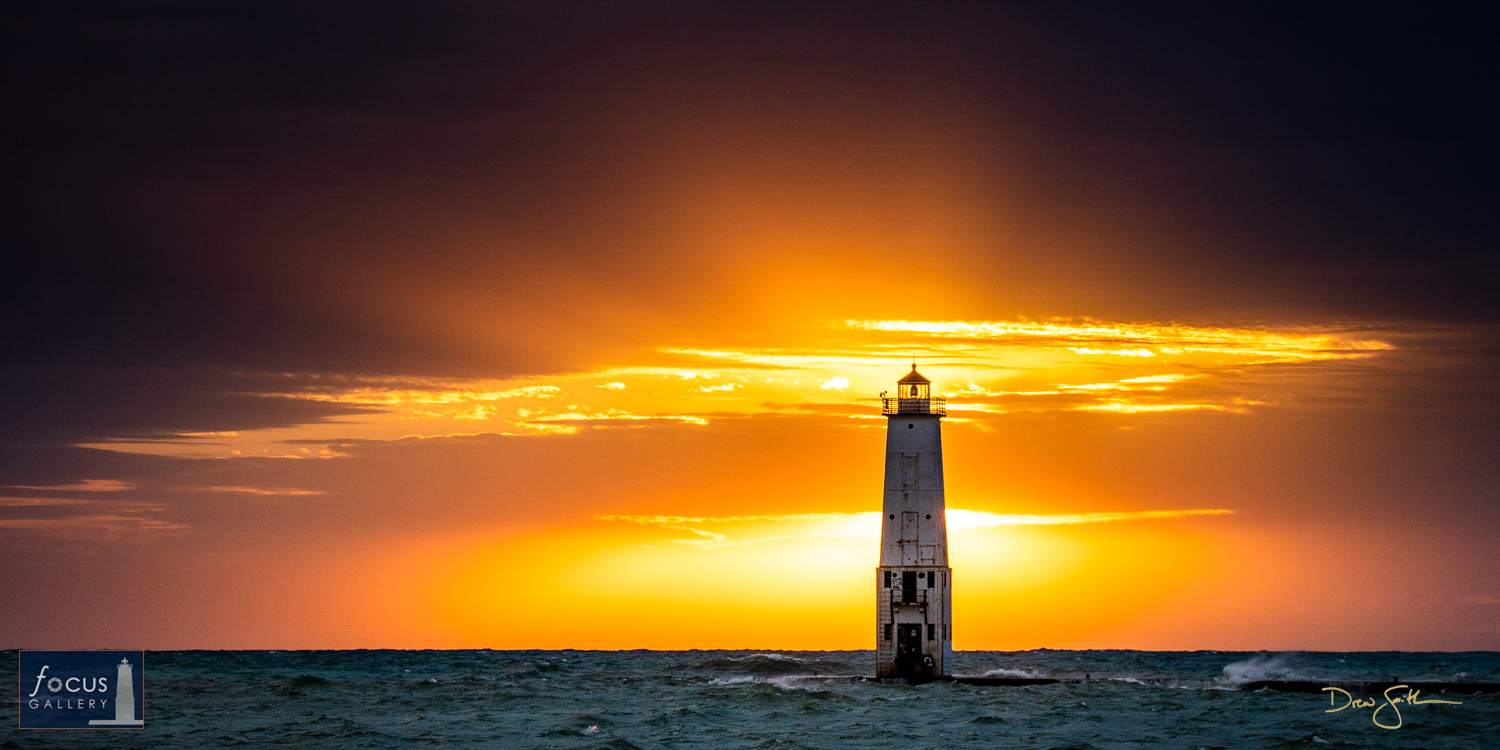 Photo © Drew Smith Sunlight beams out from behind the Frankfort Lighthouse as it breaks through clouds near the horizon, lighting...