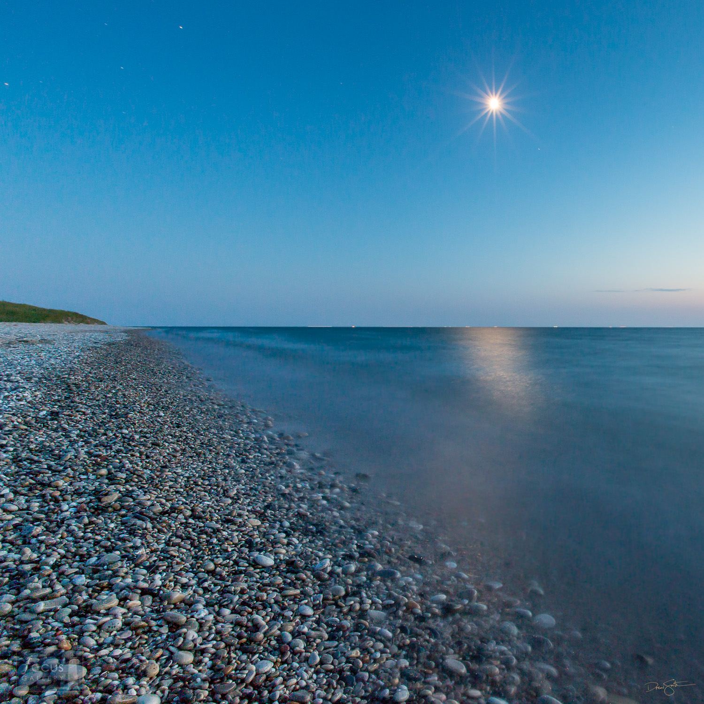 Moon shining over rocky shoreline of Lake Michigan at Point Betsie.