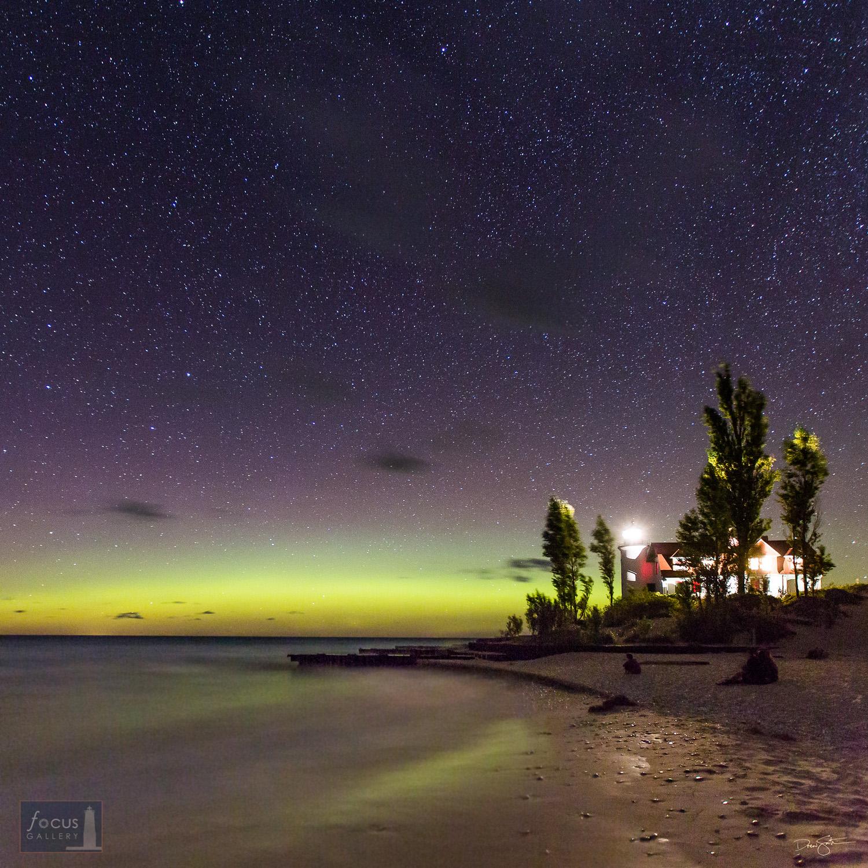 Glow of aurora borealis over Point Betsie Lighthouse and Lake Michigan.
