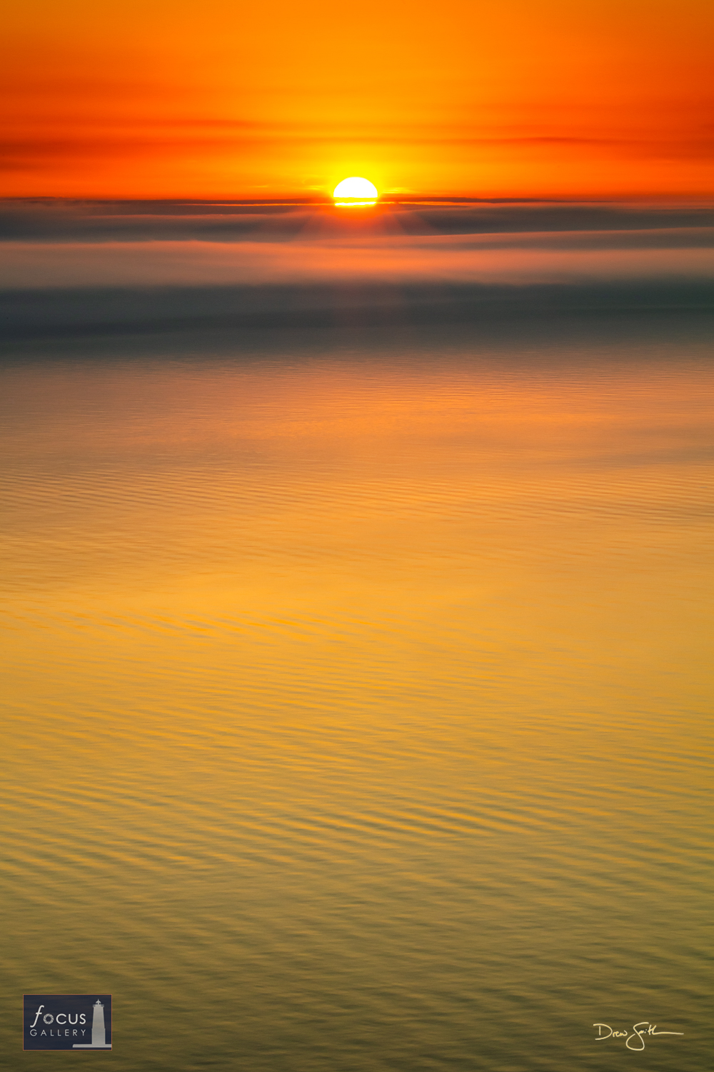 Photo © Drew Smith The sun sets into a low cloud layer over a calm Lake Michigan as seen from the bluffs north of Frankfort.
