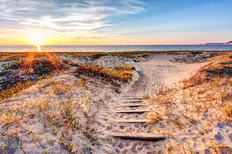 Trail leading through dunes to Lake Michigan at sunset in Sleeping Bear Dunes National Lakeshore.
