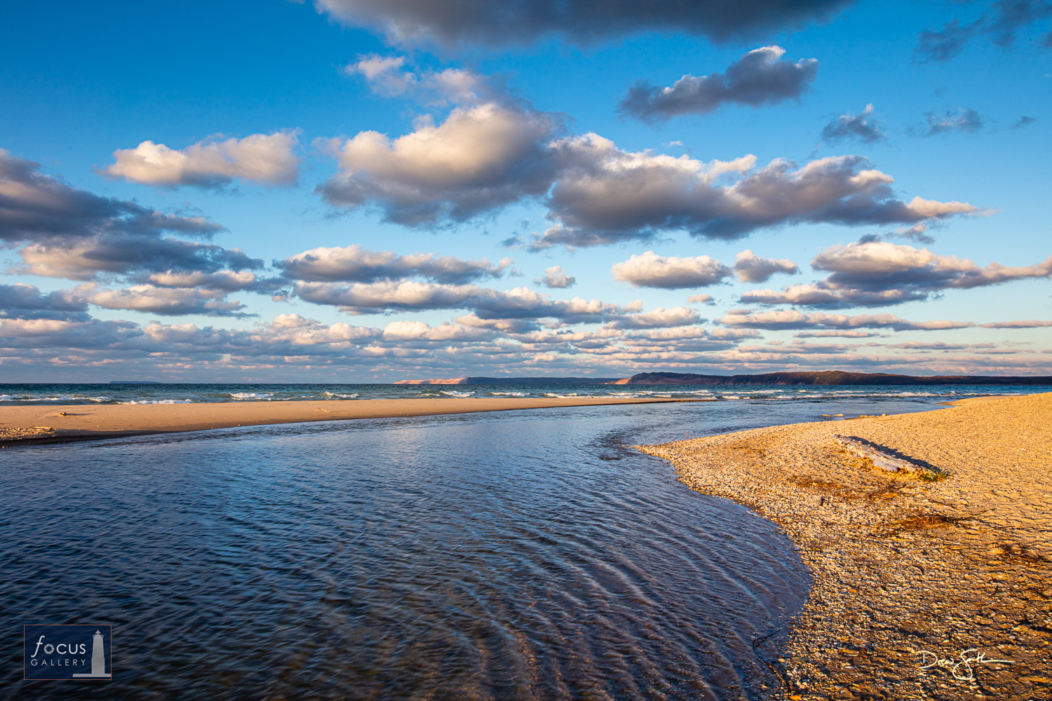 Photo © Drew Smith The Platte River flows into Platte Bay on Lake Michigan under blue skies and puffy clouds.  Platte River...