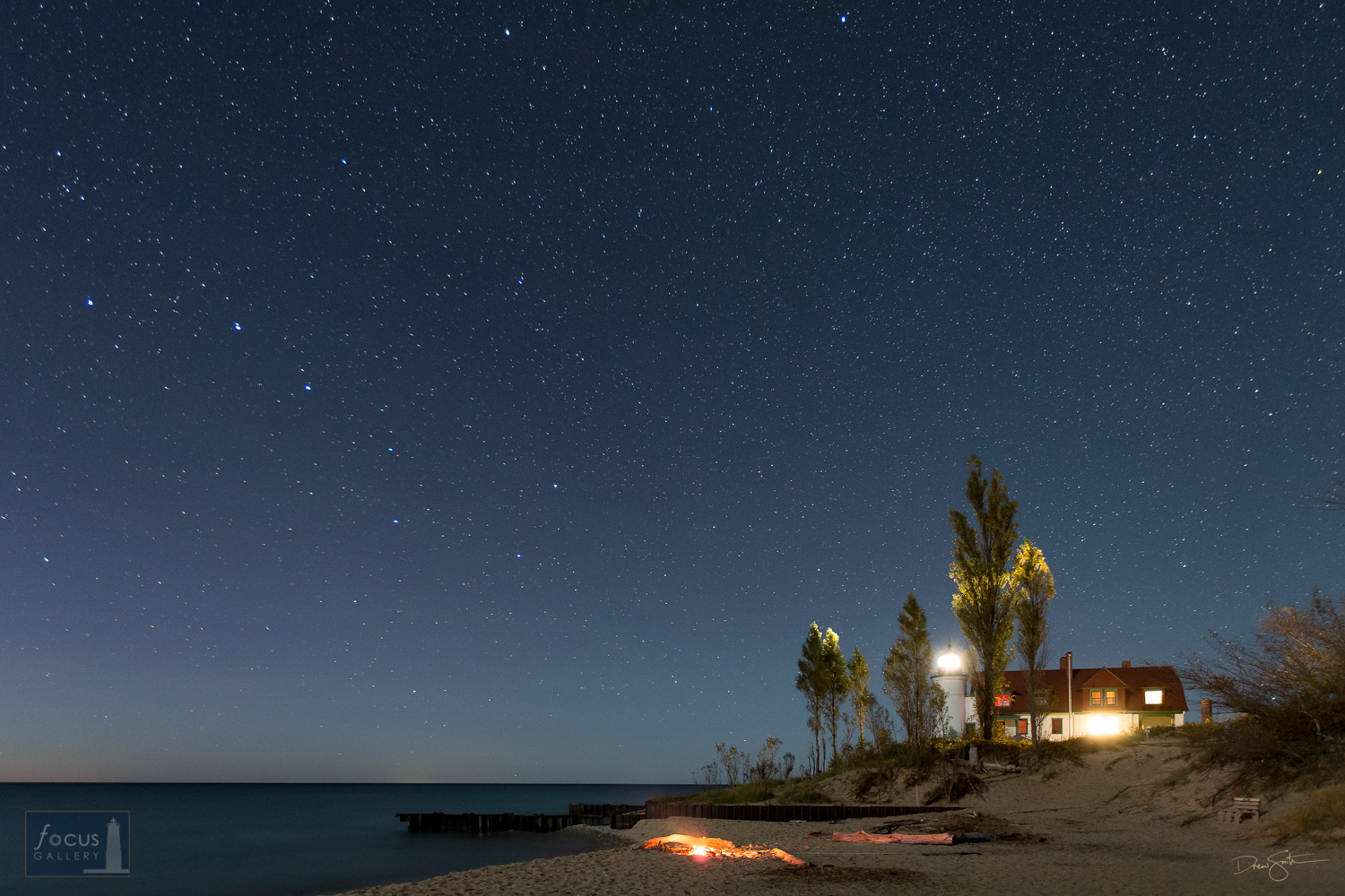 Starry sky and Big Dipper over Point Betsie Lighthouse and a fire on the beach.