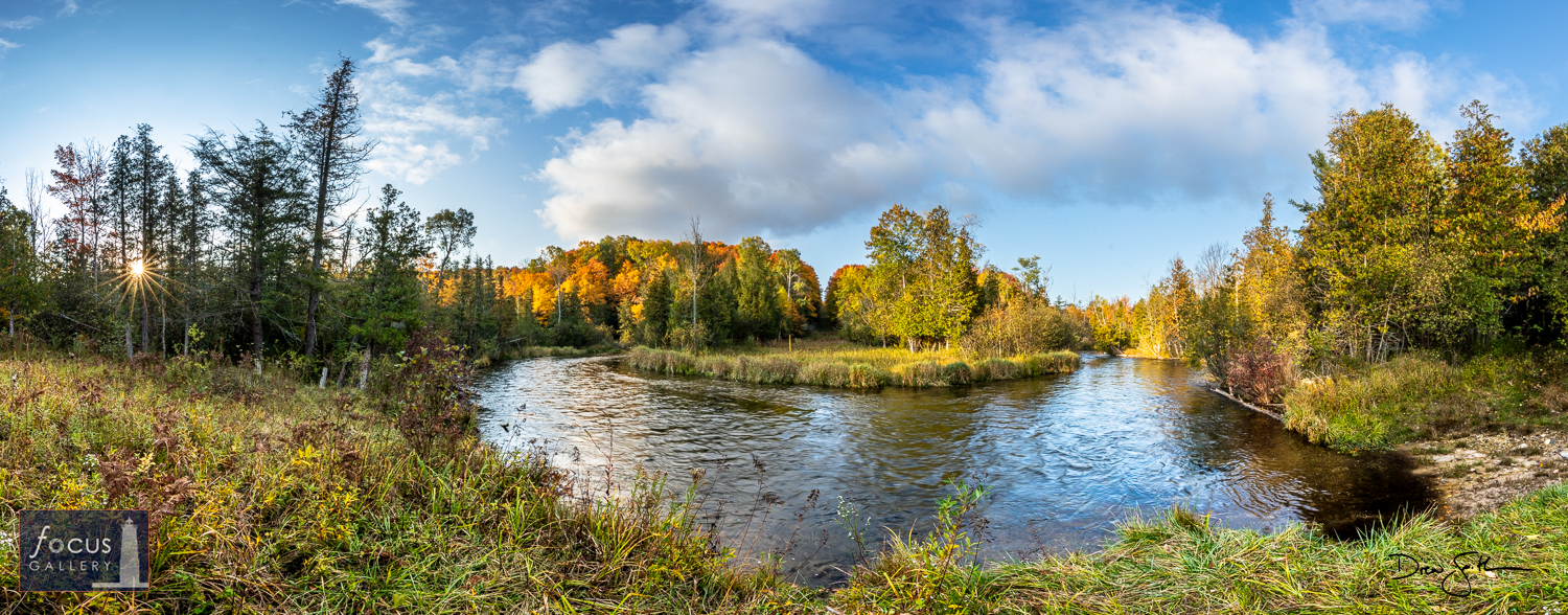 Photo © Drew Smith The rising autumn sun pokes through the forest along the banks of the Platte River near Honor, Michigan.