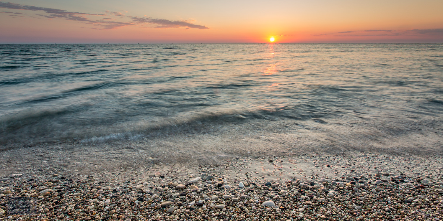 Sunset over Lake Michigan and rocky shoreline at Point Betsie.