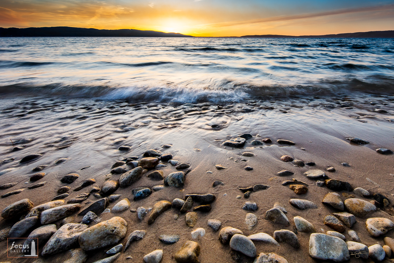Photograph of waves at sunset on a rocky Crystal Lake shoreline in Benzie County, Michigan.