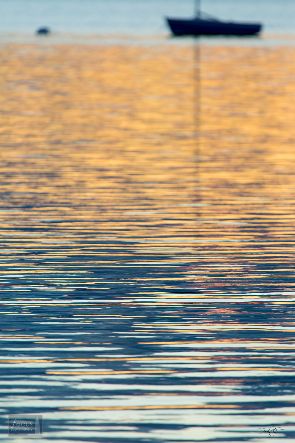 Sailboat silhouette and sunrise colors on the surface of Lake Michigan.