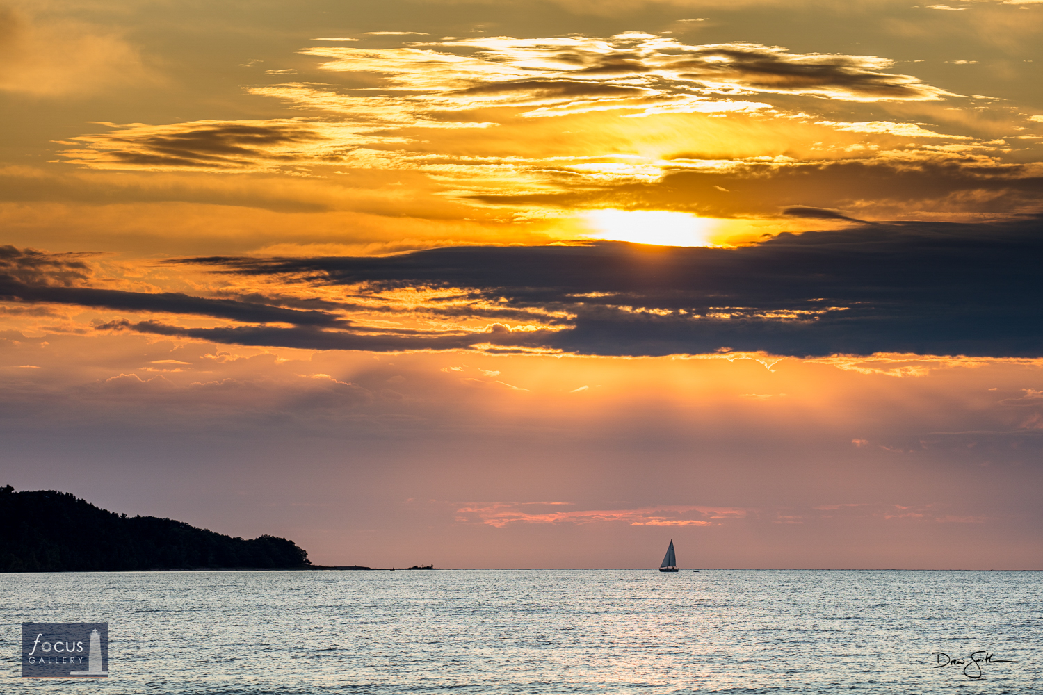 Photo © Drew Smith A sailboat passes by Platte Point as the sun competes with afternoon clouds.  Photographed from Peterson...